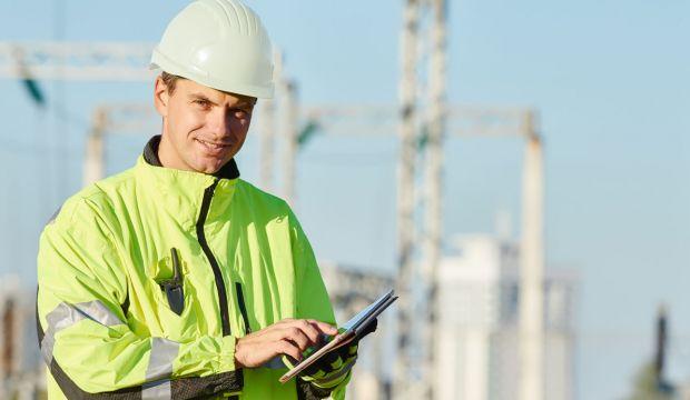 Sähkö- tai tietoverkkoalan työntekijä tabletin kanssa